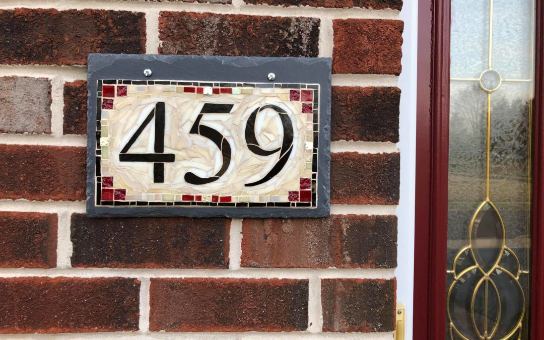 A Cream House Number Plaque with Red Accents for a Brick Home